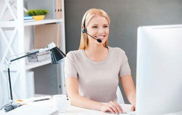 Eine junge lächelnde Frau trägt ein Headset und sitzt vor einem Computer-Monitor